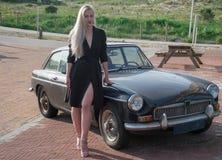 Ragazza bionda e vecchia automobile nera Immagini Stock