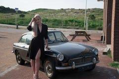 Ragazza bionda e vecchia automobile nera Fotografie Stock Libere da Diritti