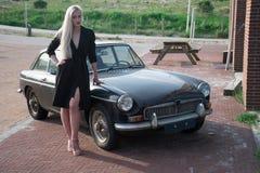 Ragazza bionda e vecchia automobile nera Fotografia Stock