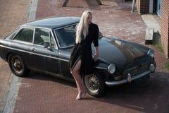 Ragazza bionda e vecchia automobile nera Immagine Stock