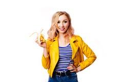 Ragazza bionda esile con una banana in sue mani su un fondo bianco isolato - Immagine fotografia stock libera da diritti