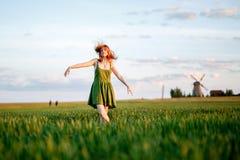 Ragazza bionda felice, ballante in un campo in pieno dei fiori gialli fondo di estate e di cieli blu fotografie stock libere da diritti