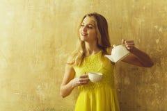 Ragazza bionda felice nelle tenute gialle tazza e teiera del vestito fotografie stock libere da diritti