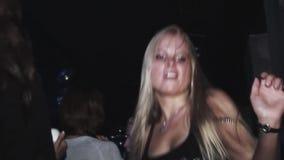 Ragazza bionda nel ballo nero della camicia sul partito in night-club Capelli di scossa celebrazione intrattenimento video d archivio