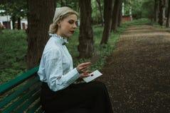 Ragazza bionda nel parco che legge una lettera di carta fotografie stock