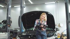 Ragazza bionda piacevole che per mezzo di un analizzatore diagnostico automobilistico stock footage