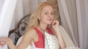 Ragazza bionda sexy a letto Sulla caduta superiore un baldacchino bianco Facendo uso dei dispositivi mobili nella vita di tutti i archivi video