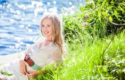 Ragazza bionda sorridente incantante che si trova sull'erba fotografia stock libera da diritti