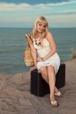 Ragazza bionda su una valigia sulla spiaggia Fotografie Stock Libere da Diritti