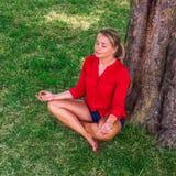 Ragazza bionda Suntanned che medita sotto un albero su erba Fotografia Stock Libera da Diritti