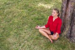 Ragazza bionda Suntanned che medita sotto un albero su erba Fotografia Stock