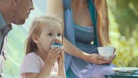 Ragazza bionda sveglia che mangia bigné all'aperto con la famiglia fotografia stock