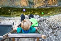 Ragazza bionda sveglia con gli occhiali da sole rosa che si siedono e che riposano su uno sdraio e su un rilassamento fotografie stock