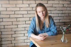Ragazza bionda triste in blusa blu che si siede alla tavola in un caffè, l Immagine Stock