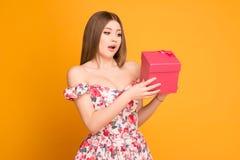 Ragazza bionda in un vestito che tiene un contenitore di regalo in sue mani fotografia stock libera da diritti