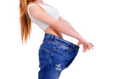Ragazza in blue jeans grandi su un fondo bianco Immagine Stock