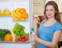 Ragazza in buona salute che prende una bottiglia di acqua dal frigorifero o completa immagine stock libera da diritti