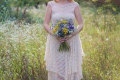 Ragazza in buona salute di giovane modo in un vestito da sposa che sta con un mazzo dei fiori luminosi in mani in natura, stile d Fotografia Stock