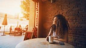 Ragazza in caffè con la tazza di caffè o il tè immagine stock libera da diritti
