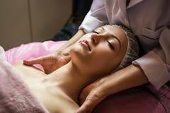 Ragazza calma che ha massaggio facciale della stazione termale nel salone di bellezza lussuoso Fotografie Stock