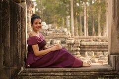 Ragazza cambogiana in vestito khmer che si siede nel terrazzo degli elefanti nella città di Angkor Fotografie Stock