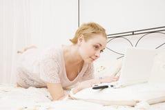 Ragazza in camera da letto con il computer portatile Immagine Stock Libera da Diritti