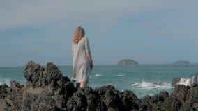 Ragazza in capo grigio che sta vicino alle onde della tempesta che colpiscono la ragazza delle rocce che guarda fuori all'oceano, archivi video