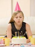 Ragazza in cappello del partito che spegne le candele Fotografie Stock