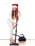 Ragazza in cappello dell'assistente di Santa con l'aspirapolvere Fotografia Stock
