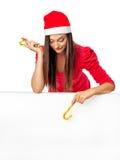 Ragazza in cappello dell'assistente di una Santa che sta vicino ad un grande bordo bianco e Immagine Stock Libera da Diritti