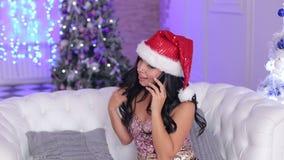 Ragazza in cappello di Santa che parla sul telefono Natale video d archivio