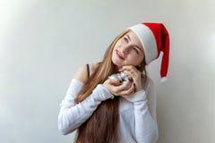 Ragazza in cappello di Santa con le palle di natale nelle mani Fotografie Stock