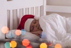 Ragazza in cappello di Santa sul letto fotografie stock libere da diritti