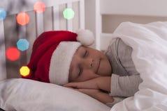 Ragazza in cappello di Santa sul letto immagini stock