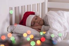 Ragazza in cappello di Santa sul letto immagini stock libere da diritti