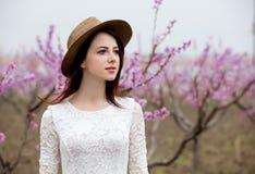 Ragazza in cappello vicino al pesco del fiore Immagini Stock