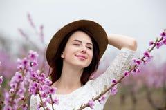 Ragazza in cappello vicino al pesco del fiore Immagine Stock Libera da Diritti
