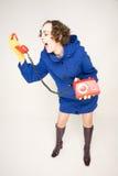 Ragazza in cappotto blu che grida in microtelefono immagini stock