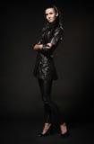Ragazza in cappotto nero di cuoio, pantaloni e scarpe, stanti su un bla Fotografia Stock