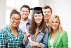 Ragazza in cappuccio di graduazione con il certificato Immagine Stock