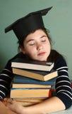 Ragazza in cappuccio di graduazione con il mucchio del libro stanco Immagine Stock