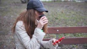 Ragazza in cappuccio facendo uso del telefono e del caffè bevente su un banco archivi video