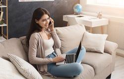 Ragazza a casa che lavora al computer portatile e che parla sul cellulare Fotografia Stock