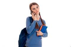 Ragazza castana abbastanza giovane dello studente con il telefono di conversazione dello zaino blu isolato su fondo bianco Fotografie Stock
