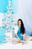 Ragazza castana all'albero del nuovo anno immagine stock