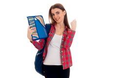 Ragazza castana allegra alla moda dello studente con lo zaino blu e cartella per i taccuini in sue mani che esaminano la macchina Fotografie Stock Libere da Diritti