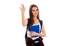 Ragazza castana arrabbiata alla moda dello studente con lo zaino blu e cartella per i taccuini in sue mani che gridano e che dist Fotografie Stock Libere da Diritti