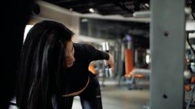 Ragazza castana caucasica che fa un allenamento del tricipite con una testa di legno sul banco Front View video d archivio
