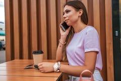 Ragazza castana che si siede nel caffè di estate Chiamate sul telefono, agli occhiali da sole della tavola e ad un tè della tazza immagine stock