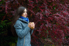 Ragazza castana che tiene tazza gialla di tè caldo Fotografia Stock